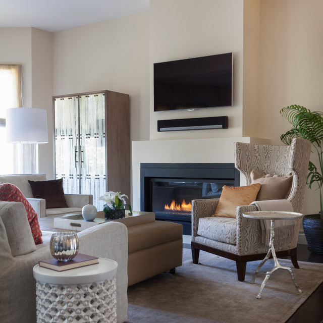 Example of a large trendy dark wood floor and brown floor living room design in San Francisco with a standard fireplace, a wall-mounted tv, beige walls and a plaster fireplace