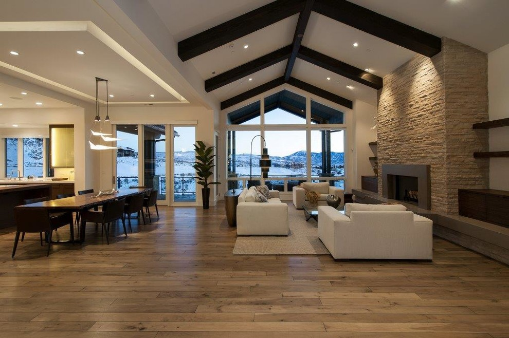Large trendy formal and open concept medium tone wood floor living room photo in Salt Lake City with white walls, a standard fireplace, a stone fireplace and no tv