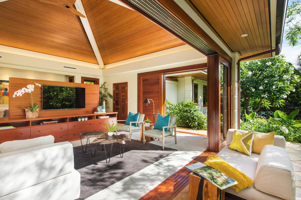 Inspiration for a large tropical open concept beige floor living room remodel in Hawaii with white walls, a wall-mounted tv and no fireplace