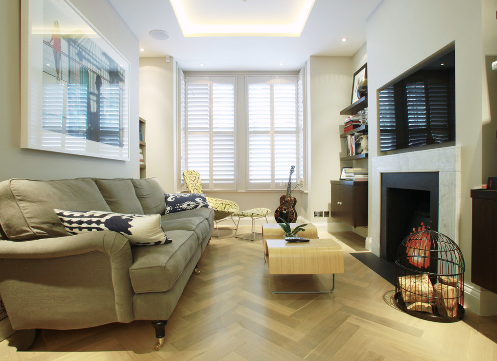 Example of a mid-sized trendy enclosed living room design in London with a standard fireplace
