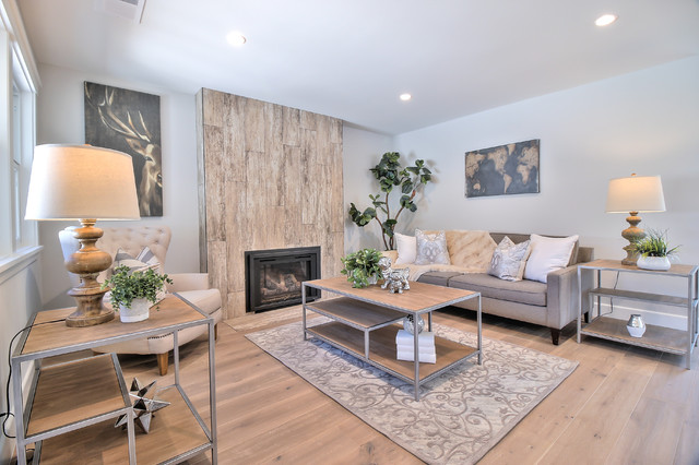 Example of a minimalist open concept light wood floor and gray floor living room design in San Francisco with gray walls, a standard fireplace and a tile fireplace