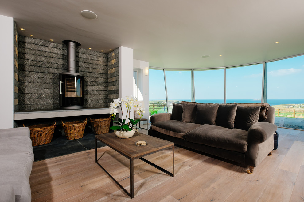Beach style formal medium tone wood floor living room photo in Cornwall with a wood stove and white walls