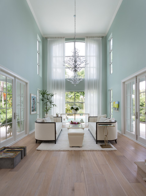 Huge island style formal and open concept light wood floor living room photo in Miami with blue walls and no tv