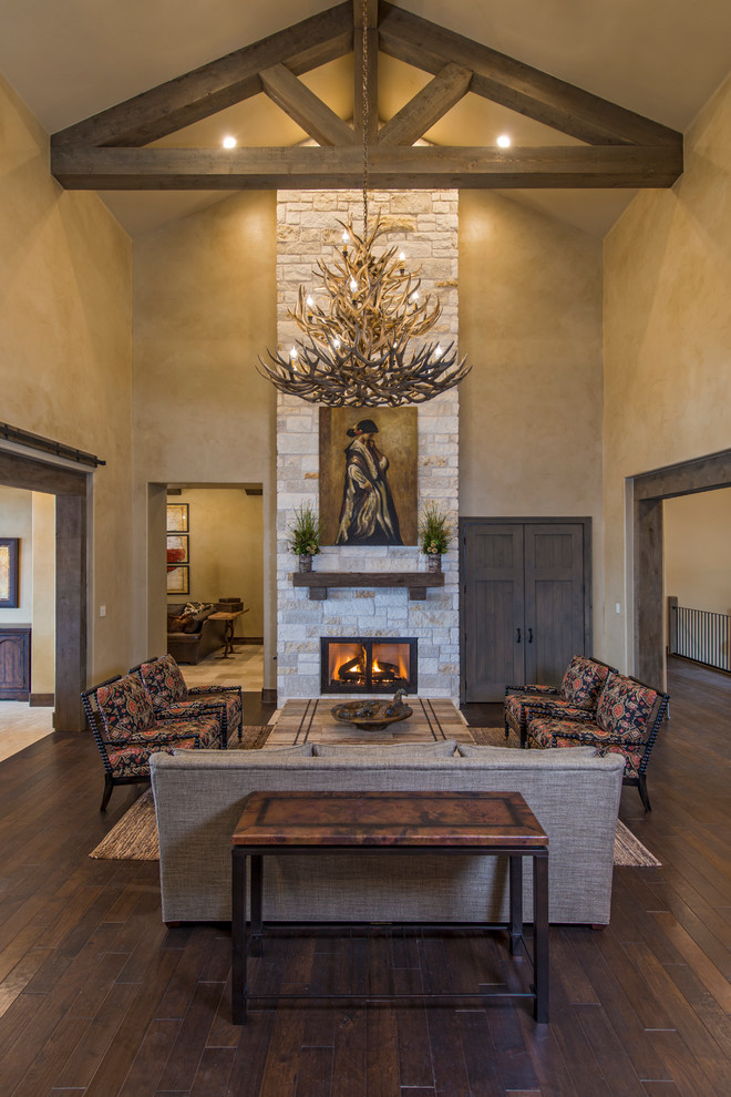 Living room - rustic formal dark wood floor living room idea in Austin with beige walls, a standard fireplace, a stone fireplace and no tv