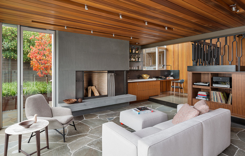 Example of a minimalist open concept slate floor living room design in Seattle with a standard fireplace, a bar and a concrete fireplace