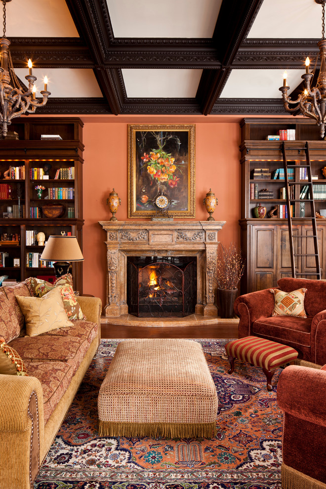Example of a classic living room library design in Toronto with orange walls and a standard fireplace