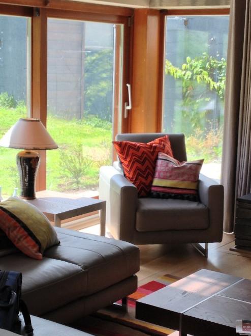 Foto de salón abierto, actual, grande, sin televisor, con paredes grises, suelo de madera clara, estufa de leña y marco de chimenea de piedra
