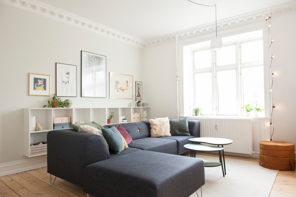 Example of a danish medium tone wood floor and brown floor living room design in Los Angeles with white walls