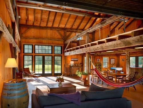 The interior of this barn conversion illustrates the use of rustic wood  beams. Photo by Masmussen / Su Architects
