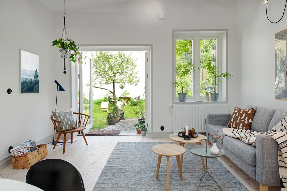 Example of a mid-sized danish open concept light wood floor living room design in Gothenburg with white walls, no fireplace and no tv