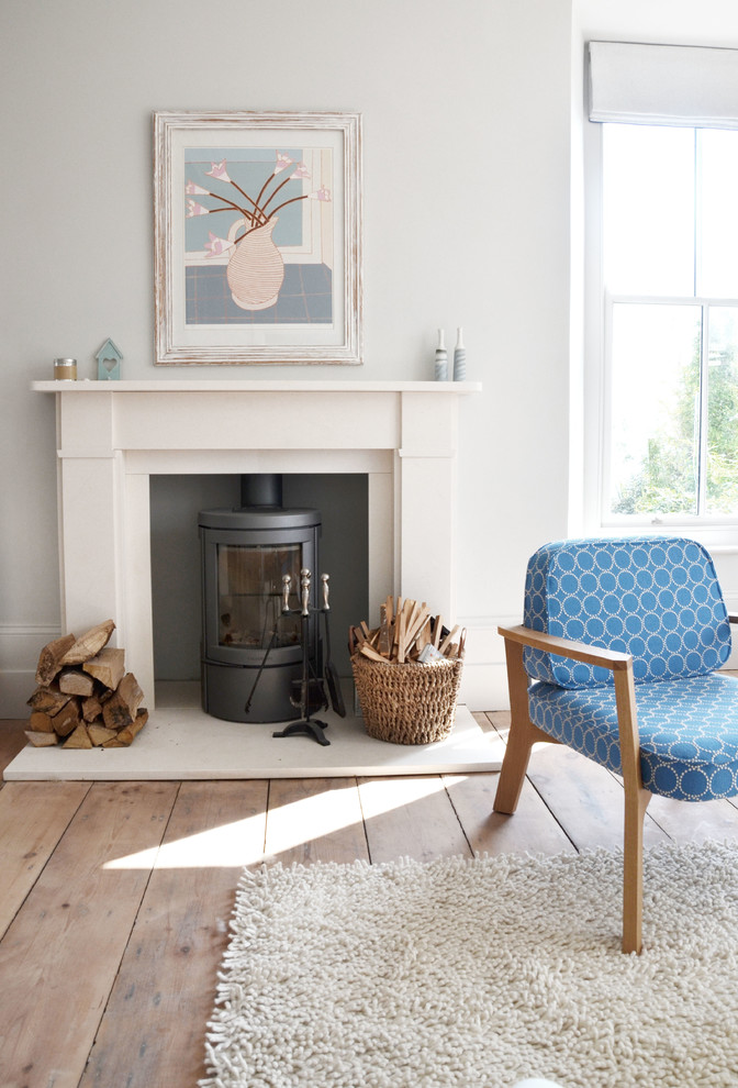 Example of a transitional light wood floor living room design in Cornwall with a wood stove and white walls