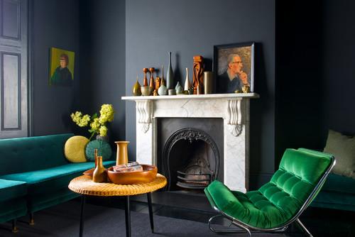 Fauteuil et canapé en velours coloré dans un salon sobre et moderne