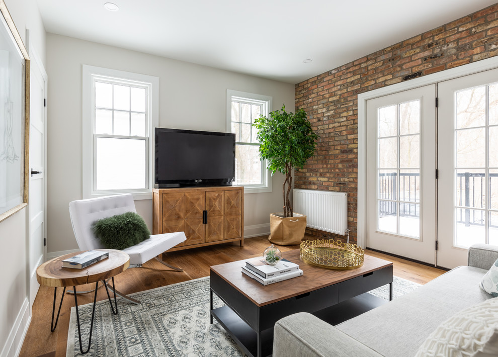 Inspiration for a small industrial medium tone wood floor and brown floor living room remodel in Toronto with white walls, no fireplace and a tv stand