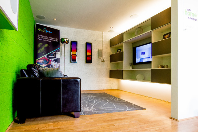 Photo of a modern living room in Hampshire with multi-coloured walls, light hardwood flooring and a built-in media unit.