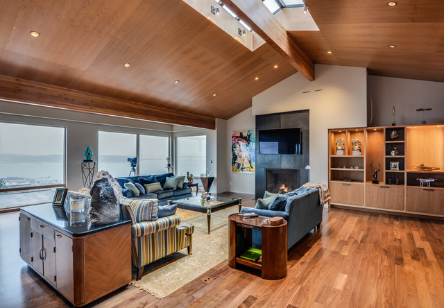 Inspiration for a large modern medium tone wood floor living room remodel in Seattle with beige walls, a standard fireplace and a wall-mounted tv