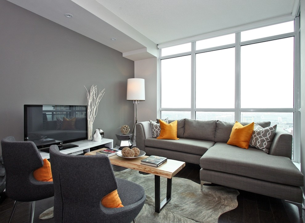 Living room - small contemporary loft-style dark wood floor living room idea in Vancouver with gray walls, no fireplace and a tv stand