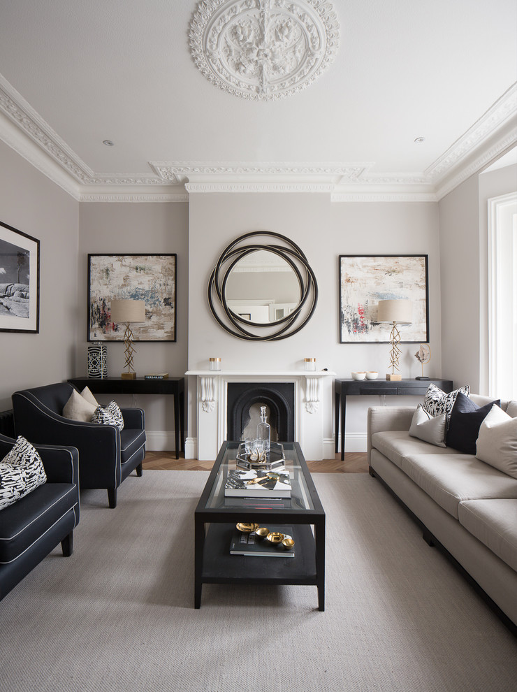 Photo of a classic formal living room in London with grey walls, medium hardwood flooring, a standard fireplace and no tv.