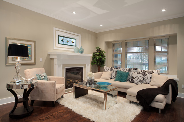 Modelo de salón actual con paredes beige, chimenea tradicional y suelo marrón