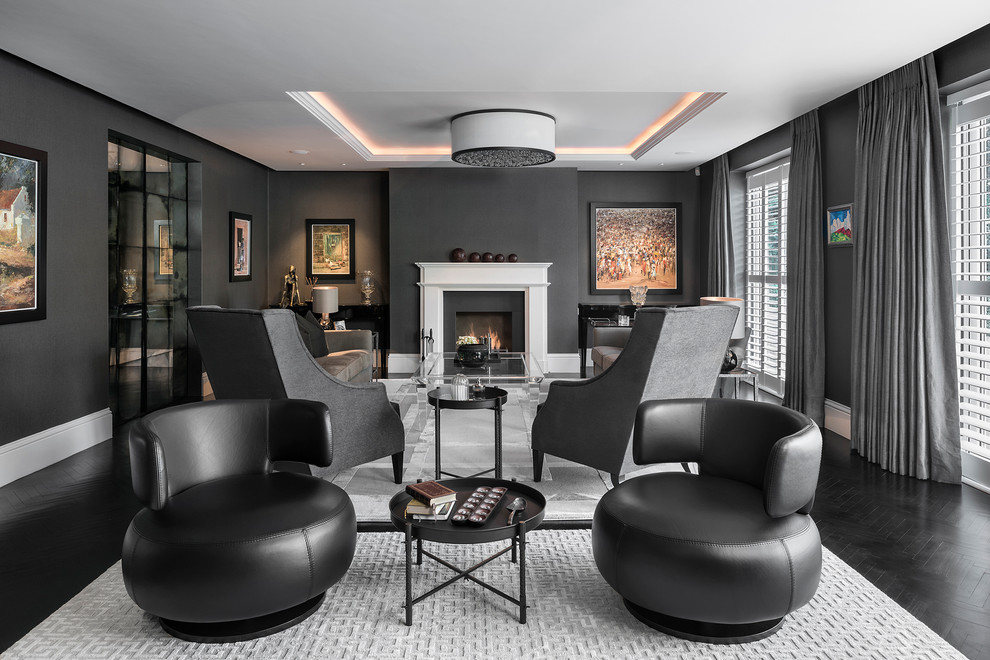 Example of a large trendy formal and enclosed dark wood floor and black floor living room design in Berkshire with black walls, a standard fireplace, a stone fireplace and no tv