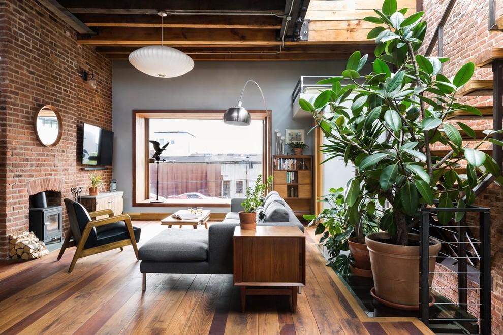 Living room - industrial medium tone wood floor and brown floor living room idea in New York with gray walls
