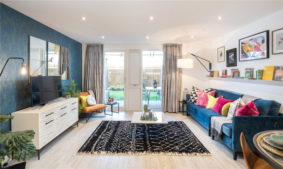 Trendy open concept light wood floor and gray floor living room photo in London with blue walls, no fireplace and a tv stand