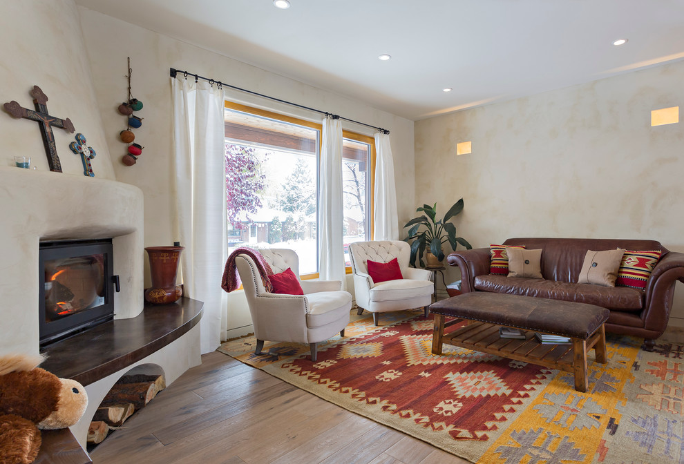 Inspiration for a mid-sized mediterranean enclosed medium tone wood floor living room remodel in Salt Lake City with beige walls, a corner fireplace and a plaster fireplace