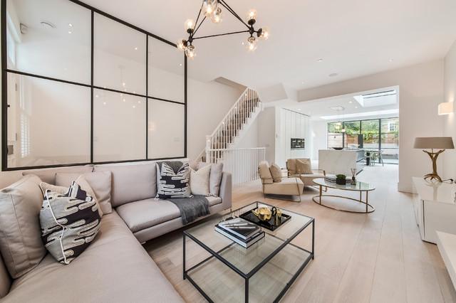 Trendy open concept light wood floor and beige floor living room photo in London with white walls