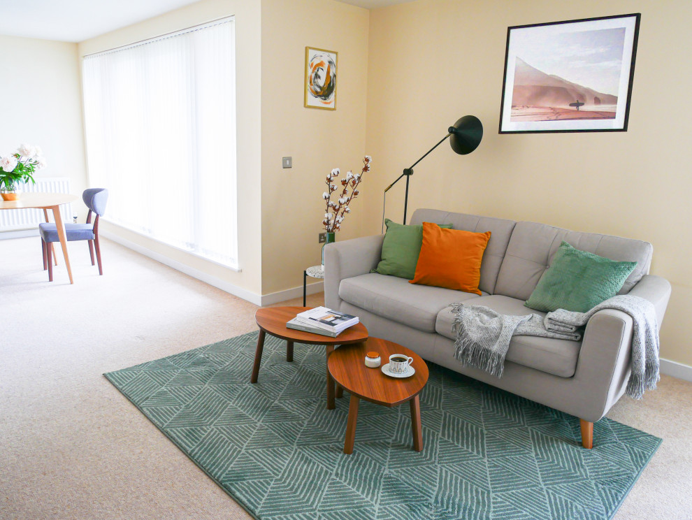Example of a mid-sized danish open concept carpeted and beige floor living room design in Edinburgh with yellow walls, no fireplace and a tv stand