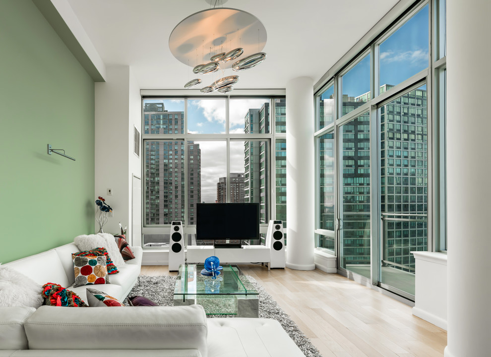 Example of a huge trendy enclosed light wood floor and beige floor living room design in New York with green walls and a tv stand