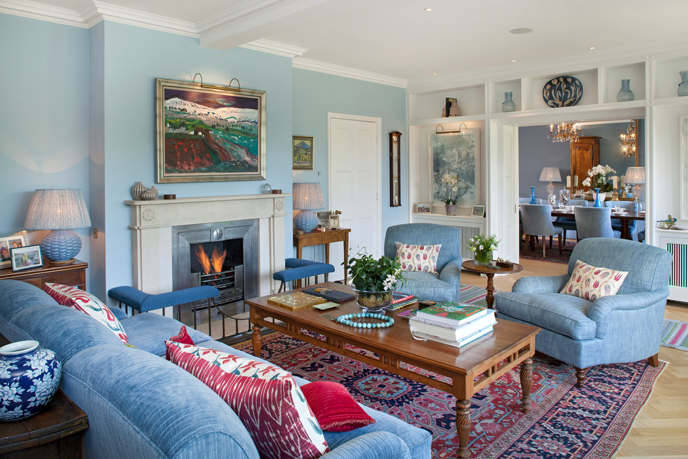 Living room - traditional light wood floor living room idea in London with blue walls, a standard fireplace and no tv