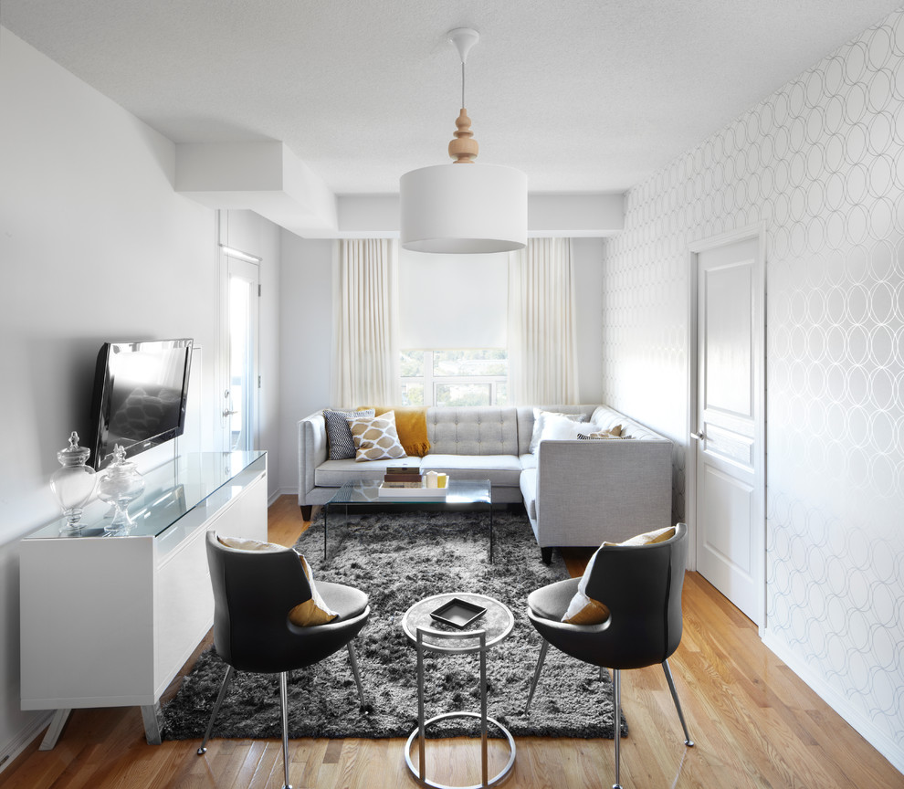 Example of a trendy medium tone wood floor living room design in Calgary with white walls and a wall-mounted tv