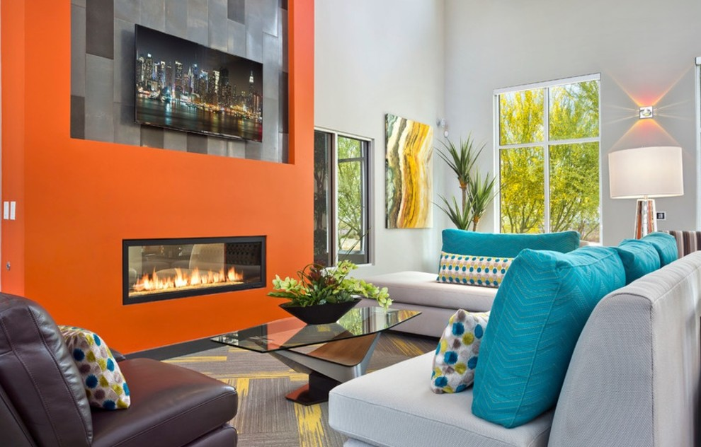 Inspiration for a mid-sized contemporary formal and open concept carpeted and gray floor living room remodel in Phoenix with orange walls, a two-sided fireplace, a plaster fireplace and a wall-mounted tv