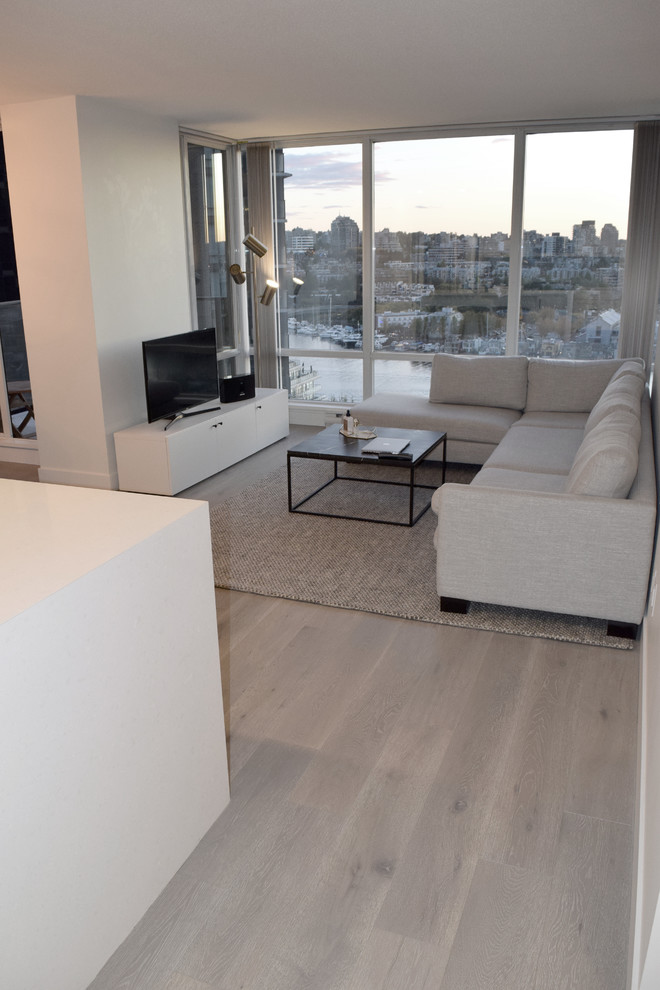 Example of a small minimalist formal and open concept light wood floor and brown floor living room design in Vancouver with white walls, no fireplace and no tv
