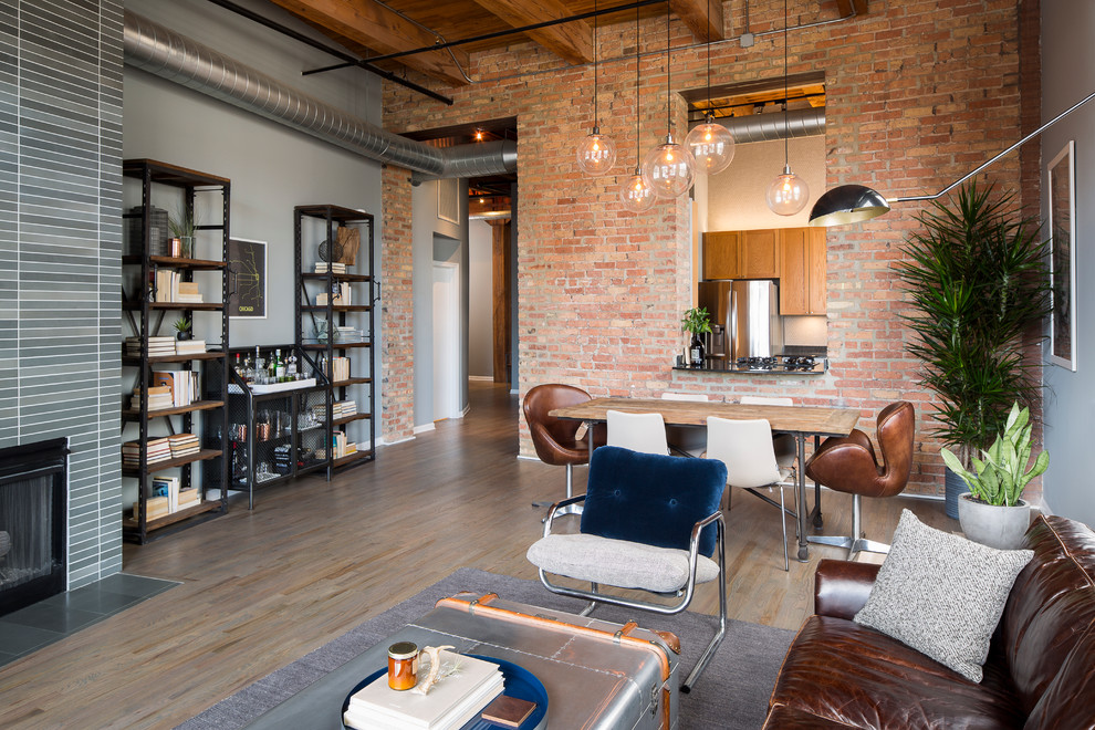 Living room - mid-sized industrial open concept dark wood floor living room idea in Chicago with gray walls and a standard fireplace