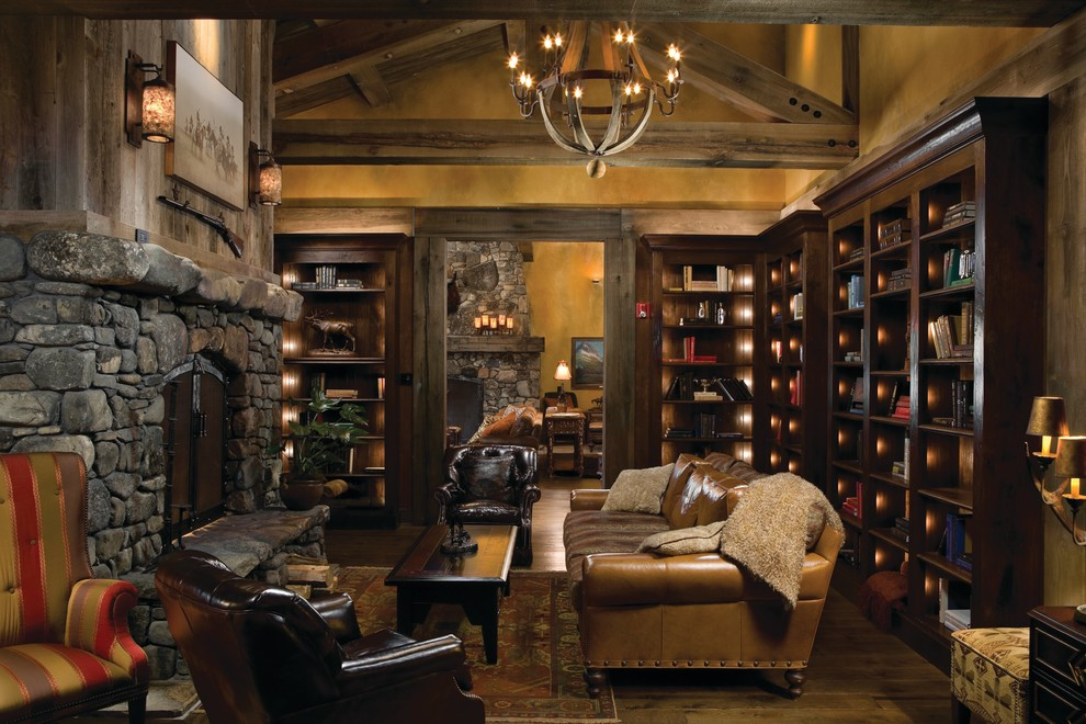Inspiration for a mid-sized rustic enclosed and formal medium tone wood floor and brown floor living room remodel in Other with a standard fireplace, a stone fireplace, beige walls and no tv