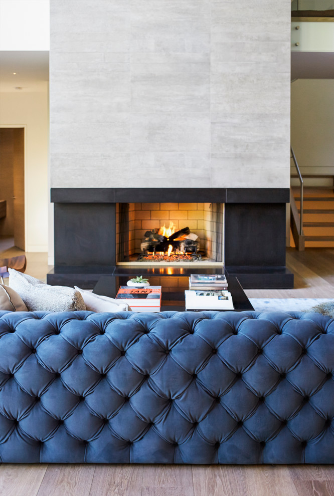 Mid-sized trendy open concept light wood floor living room photo in Vancouver with white walls, a standard fireplace, a concrete fireplace and a media wall