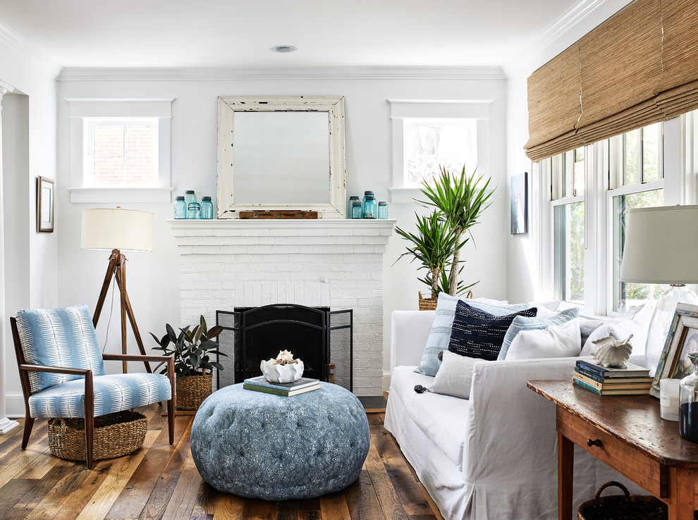 Beach style medium tone wood floor and brown floor living room photo in DC Metro with white walls, a standard fireplace and a brick fireplace