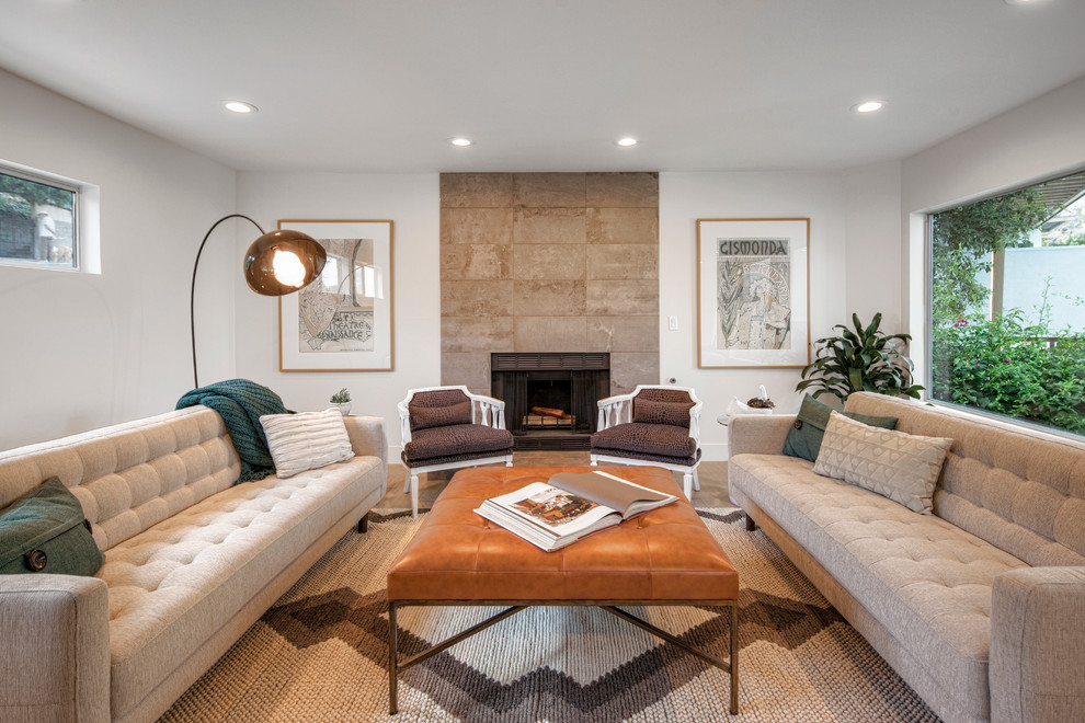 Example of a mid-sized trendy formal medium tone wood floor living room design in Los Angeles with white walls, a standard fireplace and a stone fireplace