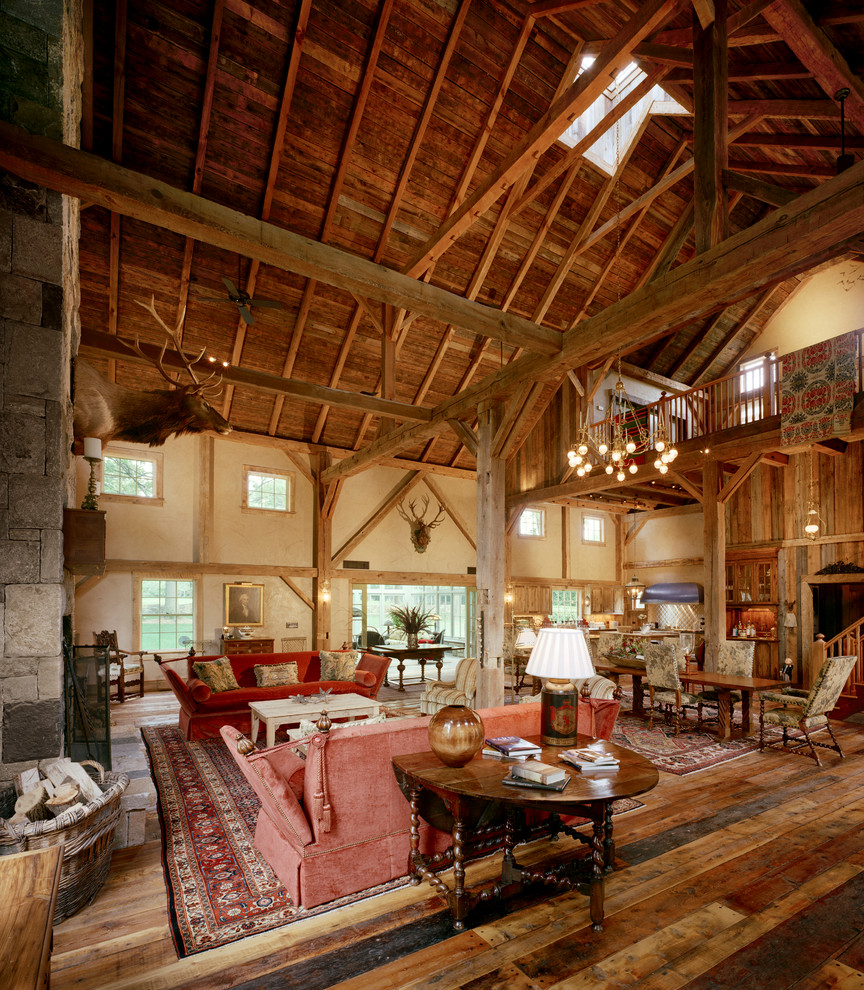 Inspiration for a large farmhouse formal and open concept medium tone wood floor living room remodel in New York with beige walls, a standard fireplace, a stone fireplace and no tv