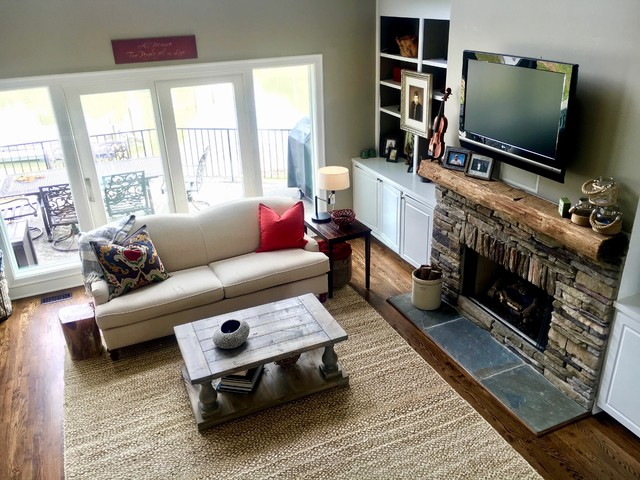 Example of a mid-sized mountain style open concept dark wood floor and brown floor living room design in Charlotte with gray walls, a standard fireplace, a stone fireplace and a wall-mounted tv