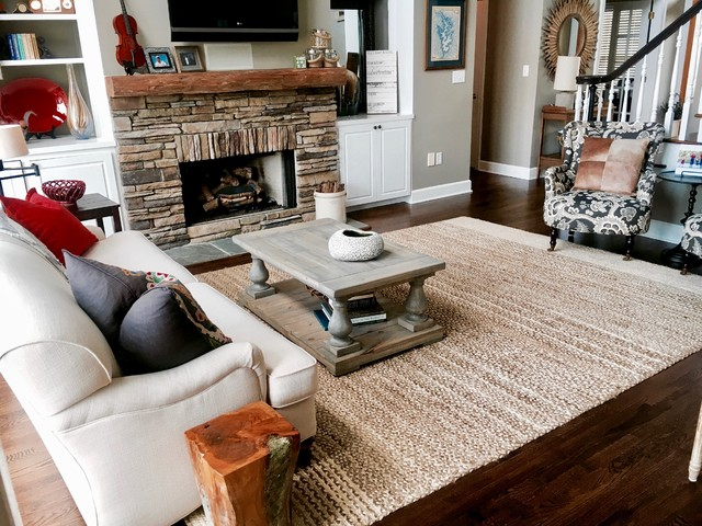 Inspiration for a mid-sized rustic open concept dark wood floor and brown floor living room remodel in Charlotte with a stone fireplace, a wall-mounted tv, gray walls and a standard fireplace