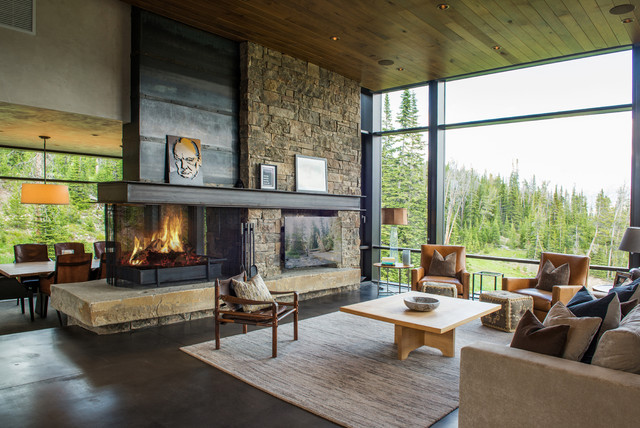 Example of a large mountain style open concept concrete floor and gray floor living room design in Other with a two-sided fireplace, a metal fireplace, a wall-mounted tv and beige walls