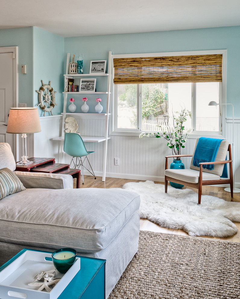 Example of a beach style open concept medium tone wood floor living room design in San Luis Obispo with blue walls