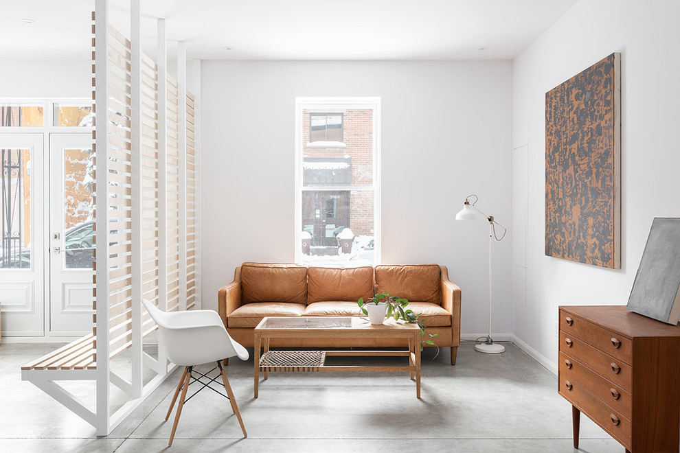 Example of a danish enclosed concrete floor and gray floor living room design in Montreal with white walls