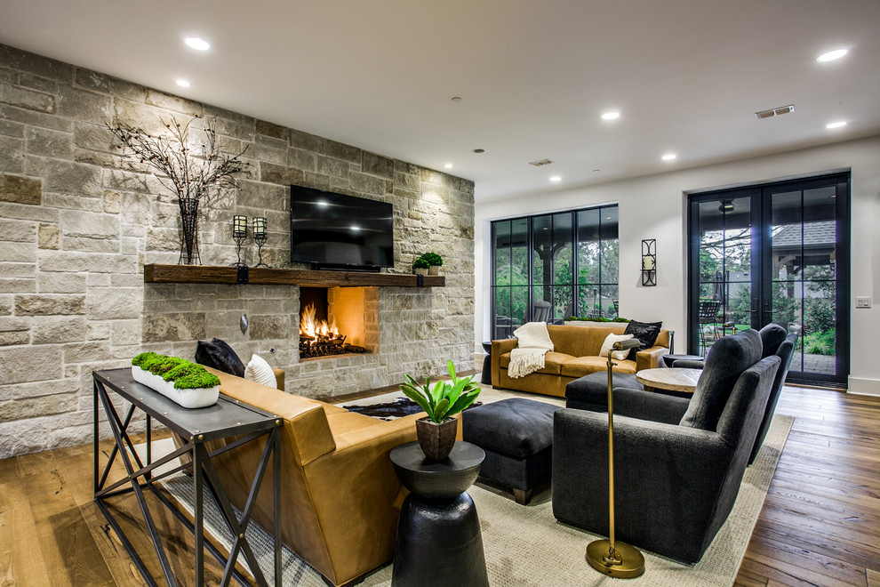 Example of a transitional medium tone wood floor and brown floor living room design in Dallas with white walls, a two-sided fireplace, a stone fireplace and a wall-mounted tv
