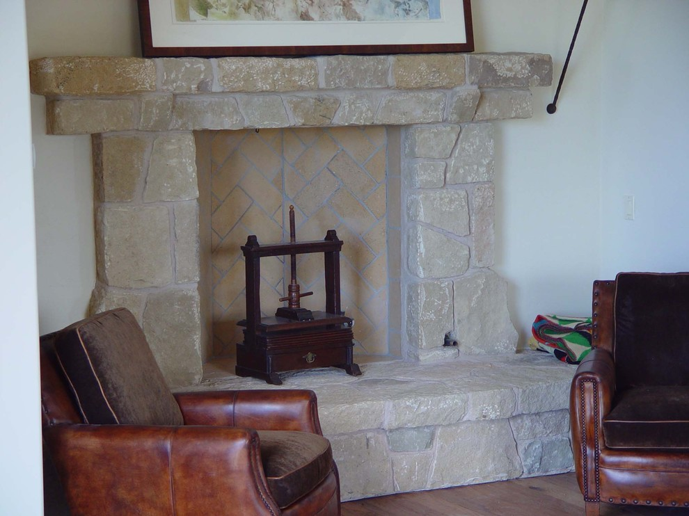 Inspiration for a mid-sized timeless formal and enclosed medium tone wood floor living room remodel in Los Angeles with white walls, a standard fireplace, a stone fireplace and no tv