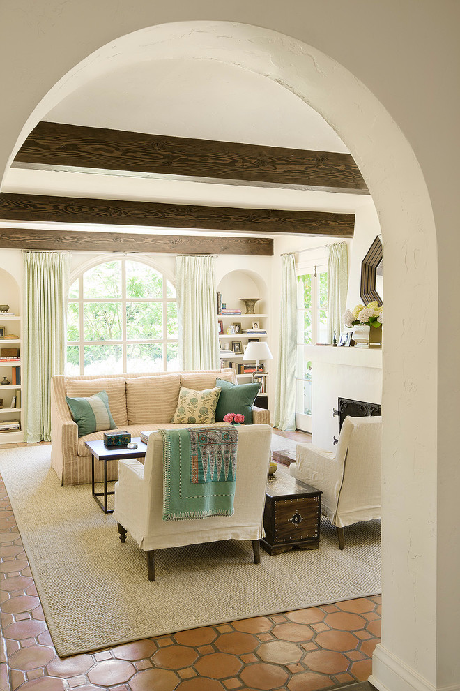 Inspiration for a large mediterranean enclosed terra-cotta floor living room remodel in Los Angeles with white walls and a standard fireplace