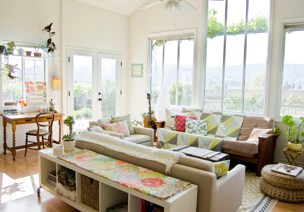 Living room - cottage medium tone wood floor living room idea in Santa Barbara with a music area and white walls