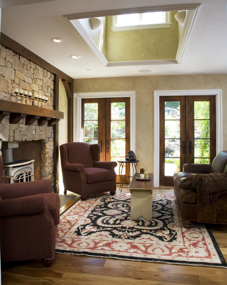 Example of a classic living room design in San Francisco with a stone fireplace and a wood stove