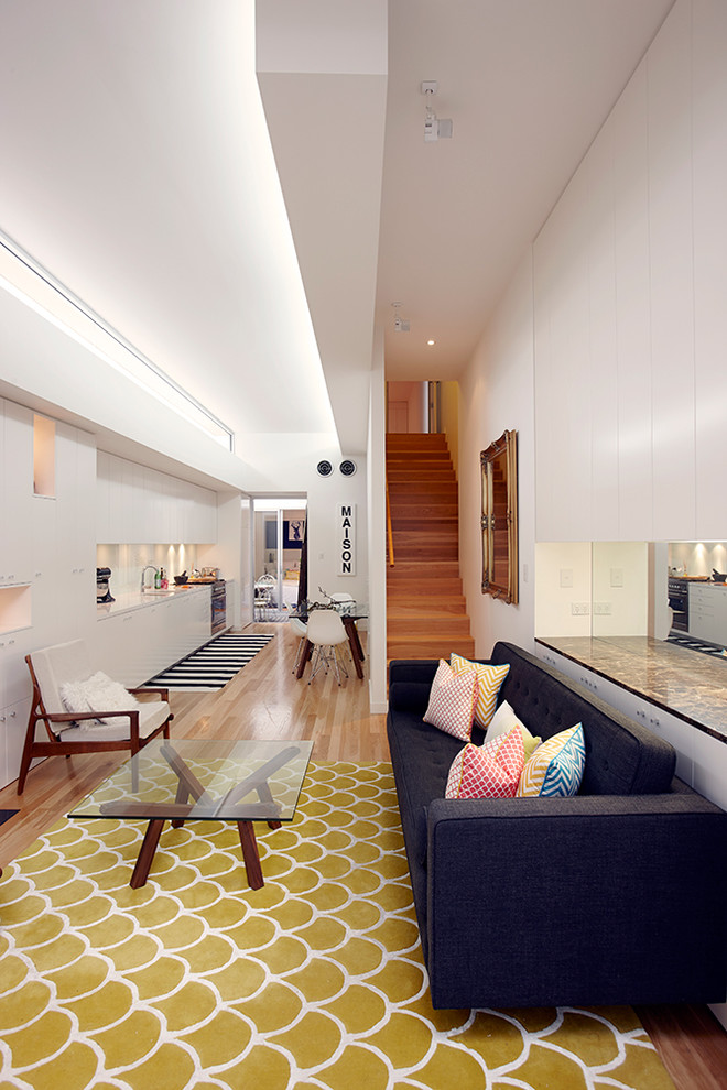 Small danish open concept light wood floor living room library photo in Sydney with white walls